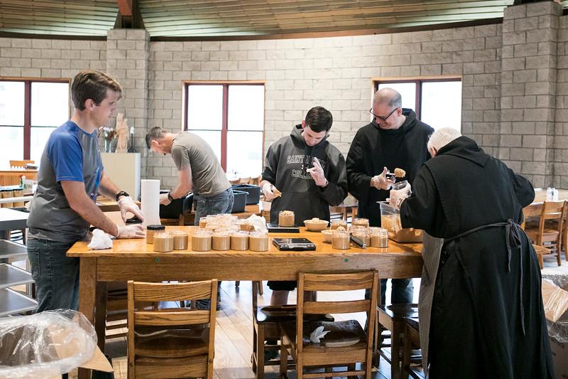 Saint Meinrad monks Br. Kolbe Wolniakowski, Br. Nathaniel Szidik, Br. John Mark Falkenhain, Fr. Prior John McMullen, Novice Christian Lumsden, and Br. Aloysius Saracen work together to jar Peanut Brother on November 9, 2018 inside the monastery.