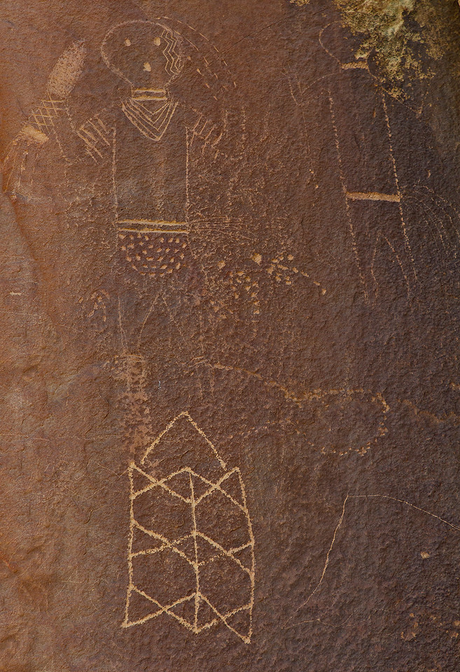 "The two petroglyph figures represent the Navajo ""Hero Twins,"" born of ""Changing Woman."" ""Monster Slayer, ""with his knife, is on the left. The right-hand figure represents the other twin, ""Born for Water."" I don't know what the geometric figure might represent."