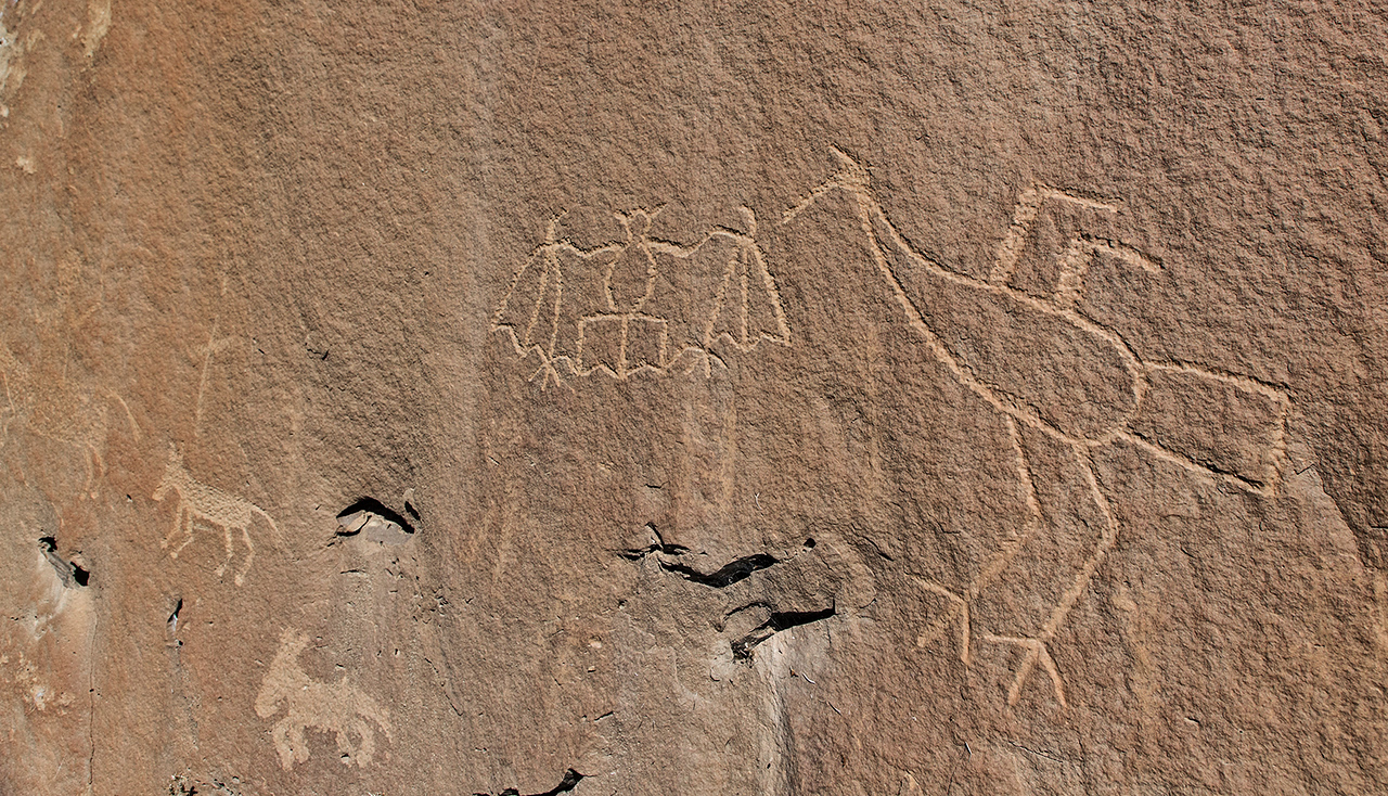 Petroglyphs of a crane, bat, and three horses, one with a rider (faintly seen on the left edge).