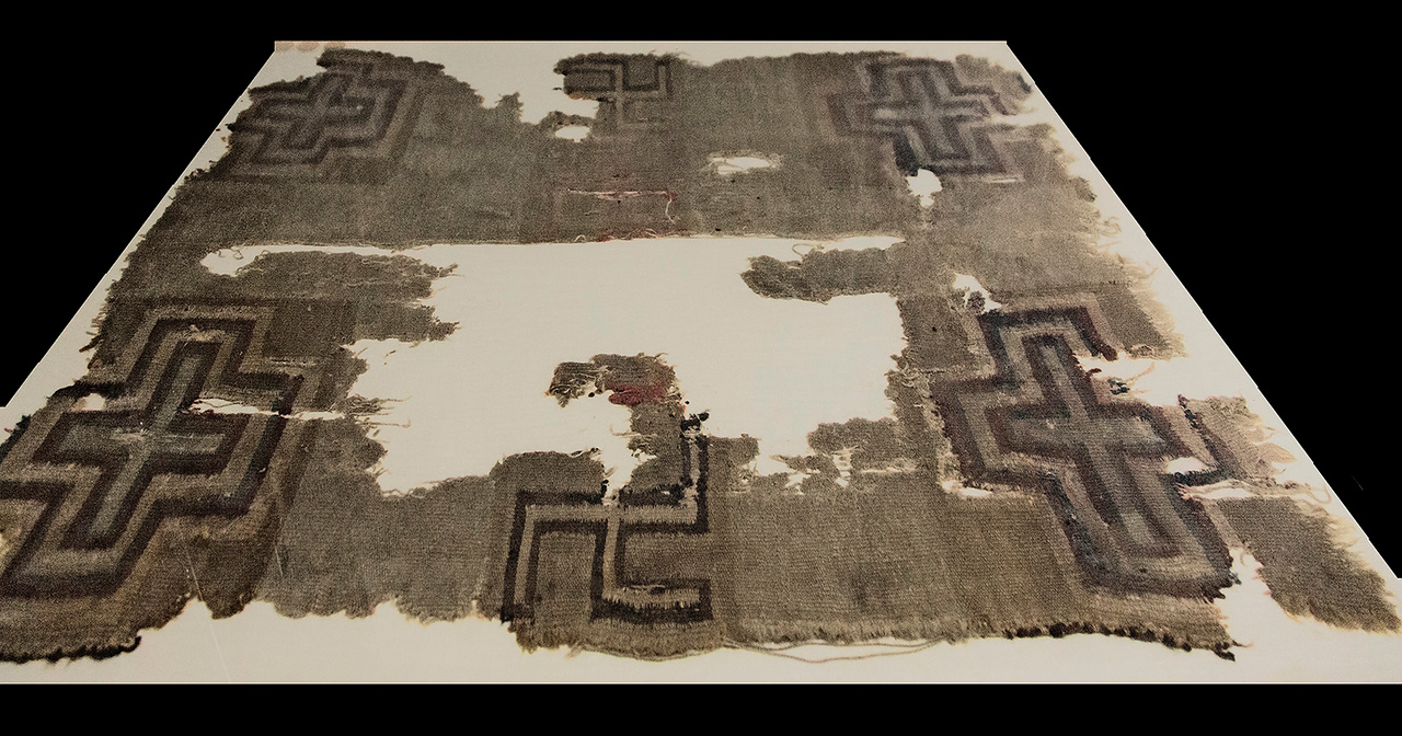 A very old piece of fiber fabric. Note that the symbol at the bottom is an ancient symbol found both in Native American and East Indian art. The Nazi swastika is a mirror image of this symbol.