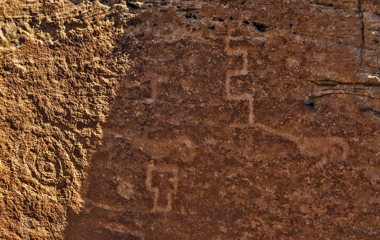 On the canyon wall Below Tower Point are several petroglyphs. On the left is a spiral. In the middle a parakeet sits on a T-doorway figure, with another parakeet on the right.