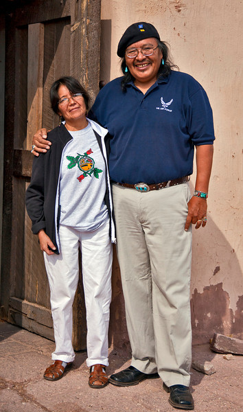 Zuni artist Ken Seowtewa and his wife in front of the Zuni Mission. He assisted his father in the painting of the larger-than-life-size Kachina figures on the mission's interior walls. Note: photography is not permitted inside the mission.
