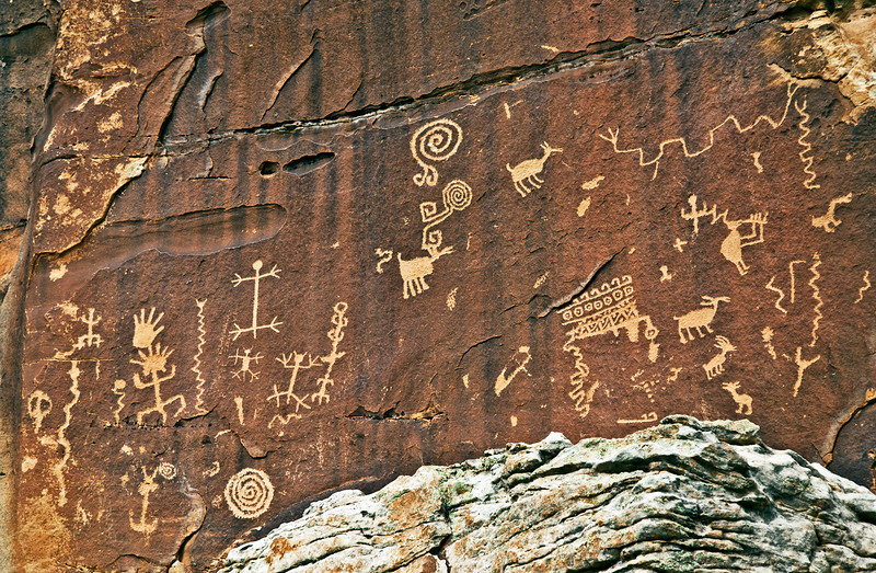 The next petroglyphs are on the red wall of the upper cliff that was mentioned earlier. Some of the figures are easily identifiable. Kokopelli appears again.