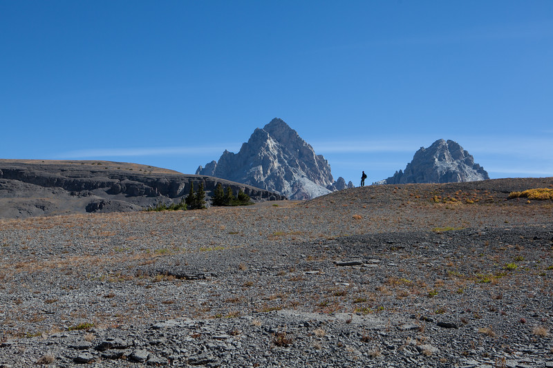 10. Archaeologist Rebecca Sgouros admires the back side of the Grand and Middle Teton while searching for prehistoric sites above treeline in the Teton Range, Wyoming