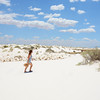 Girl on hiking trip  waking  to the sand dunes, beautiful  desert landscape.  Blue sky with clouds in the background. White Sands National Monument, New Mexico, USA