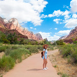 Smiling girl on a hiking trai. Girl with backpack hiking in red mountains. Zion National Park, Utah, USA