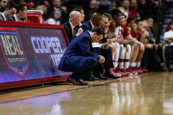 Head Coach Archie Miller kneels on the sideline during Indiana's game against the Indiana State Sycamores. The Hoosiers lost to the Sycamores 69-90. This marked Millers first regular season game as head coach of the Hoosiers.