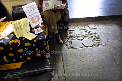 HC - PARANORMAALBEURS IN GROTE KERK - Veel tarotkaartlezers in de Grote Kerk. Als er geen klant is even een krantje lezen boven op een grafsteen. - DEN HAAG 4 JANUARI 2003 - FOTO: NICO SCHOUTEN
