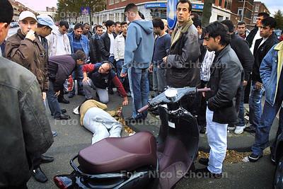 ERNSTIG SCOOTER ONGELUK TREKT VEEL PUBLIEK - Op de Vaillantlaan in Den Haag is zaterdag rond 18:00 bij een aanrijding tussen een auto en een scooter, de scooterrijder  (een jongeman) ernstig gewond geraakt. Direct stroomde van alle kanten het kruispunt vol met toeschouwers. De Politie had grote moeite om de menigte uiteen te drijven om het verkeer doorgang te verlenen. DEN HAAG 10 OKTOBER 2003 - FOTO: NICO SCHOUTEN