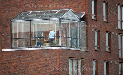 """LEKKER DARTEN OP JE BALKON - Buiten waait het windkracht 6 maar toch kan deze bewoner van de Vinexwijk, het Wateringseveld (Perzikkenpad) op zijn balkon darten dankzij deze """"westlandse balkonkas"""" - DEN HAAG 7 JANUARI 2004 - FOTO NICO SCHOUTEN"""