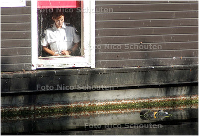 AD/HC - LIJK IN WATER VEENKADE - Een politieachente kijkt uit het raampje van een woonboot naar het lijk dat in het water ligt - DEN HAAG 16 SEPTEMBER 2008 - FOTO NICO SCHOUTEN