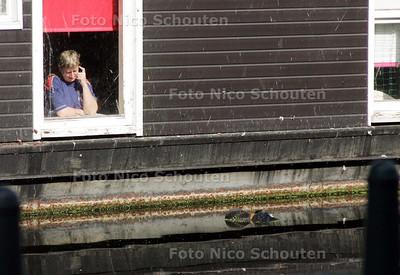 AD/HC - LIJK IN WATER VEENKADE - Een bewoonster van een woonboot kijkt, terwijl zij een telefoontje pleegt, uit het raampje naar het lijk dat in het water ligt - DEN HAAG 16 SEPTEMBER 2008 - FOTO NICO SCHOUTEN