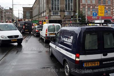 GEDWONGEN VERKEERSOVERTREDING. Door de werkzaamheden aan de tramrails in de Vondelstraat mag het verkeer vanuit het centrum niet meer rechtdoor. Toch is de verplichte rijrichting, volgens het verkeersbord, rechtdoor. Dus moeten de automobilisten, of ze het nu willen of niet, een verkeersovertreding maken... - DEN HAAG 5 NOVEMBER 2009 - FOTO NICO SCHOUTEN