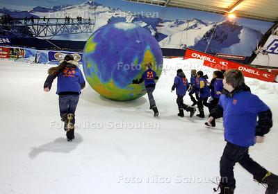 Schoolkids duwen grote wereldbol tegen helling sowworld op om de wereld hogerop te helpen ; Project van Edukans - SNOWWORLD - ZOETERMEER 11 JANUARI 2010 - FOTO NICO SCHOUTEN