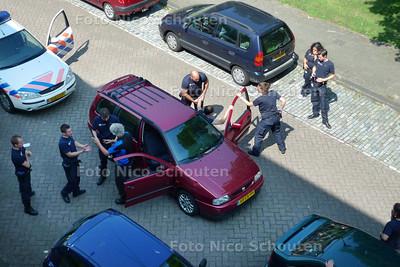 """STOP POLITIE !!! De Robijnhorst in het rustige Mariahoeve word deze morgen plotseling opgeschut door een wilde arrestatie. Van de schrik vliegt de koffie uit de kopjes. """"Wat is daar aan de hand?"""" De bewoners staan met kloppend hart op de balcons en achter de ramen. """"Maar wat is dat? De arrestanten hebben politiekleding en kogelvrije vesten aan! Dit is echt hot... er worden politiemannen ingerekend!!!"""". Maar plotseling beginnen ze te laggen, de boeien gaan weer af, iedereen stapt weer in. Geintje? Och... gewoon een oefening. Toch wel even schrikken hoor... - DEN HAAG 23 JUNI 2010 - FOTO NICO SCHOUTEN"""