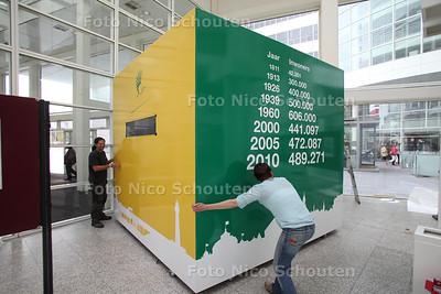 In het Atrium van het stadhuis wordt gewerkt aan het installeren van de kubusklok die aftelt naar de 500.000e inwoner - DEN HAAG 12 AUGUSTUS 2011 - FOTO NICO SCHOUTEN