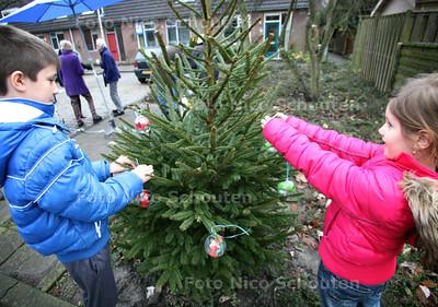 Inwijding wensboom(pje) op de Meunsloot (wijk Seghwaert) - Het was wel even zoeken. De mensen en de parasollen zag ik wel maar waar was die kerstboom. Ah daar staat ie. Een piepklein sparretje in het plantsoen. Daan en Anna hanger er wat plastic kerstballen met briefjes erin aan de takjes - ZOETERMEER 14 DECEMBER 2011 - FOTO NICO SCHOUTEN