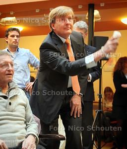 Prins van Oranje aan Nederland Cares en start campagne NL DOET. Willem Alexander speetl een spelletje bowling met de nintendo whi - DEN HAAG 1 FEBRUARI 2011 - FOTO NICO SCHOUTEN