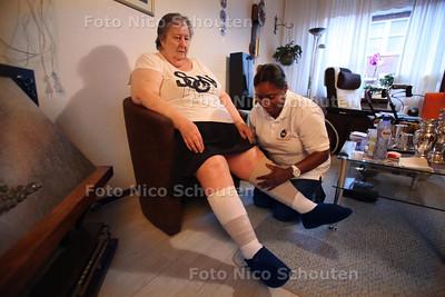 Mevrouw Kater. Zij kreeg jarenlang thuiszorg bij H+B, dat is failliet gegaan en nu is ze overgegaan naar WZH. Thuishulp Ivelin zwagtelt haar benen - DEN HAAG 12 JULI 2011 - FOTO NICO SCHOUTEN