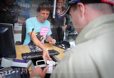 """Jochem Myjer verkoopt het eerste kaartje aan de kassa van de Koninklijke Schouwburg bij de start van de kaartverkoop van """"Even geduld a.u.b."""" - DEN HAAG 11 JUNI 2011 - FOTO NICO SCHOUTEN"""