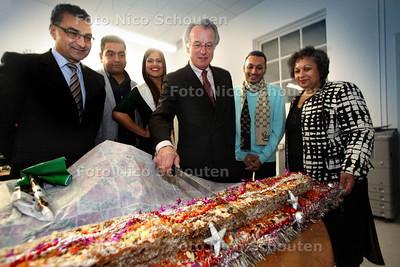Tijdens een bijeenkomst ondernemers, snijdt van Aartsen een Surinaamst brood aan. Rechts van hem de surinaamse maker - DEN HAAG 12 DECEMBER 2012 - FOTO NICO SCHOUTEN