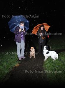 In de strokenbuurt hebben ze de verlichting in een groenstrook weggehaald, waardoor het onveilig is. Mensen lopen nu met mijnwerkerslampjes hun hond uit te laten. Louise van den Bosch (R) en buurvrouw laten met zaklampjes in de hand/op hoofd de hond uit. ZOETERMEER 14 DECEMBER 2012 - FOTO NICO SCHOUTEN