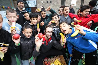 Medewerker van de Digros, Tephan de Ridder en de sportcoach uit de wijk, delen fruit uit aan kinderen tijdens een tennistournooi - ZOETERMEER 28 FEBRUARI 2014 - FOTGRAFIE NICO SCHOUTEN