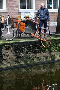 Horecaman Ferry van Winden bij een vervallen oranjekleurige bakfiets die al ruim een jaar over de rand van een Delftse gracht bungelt - DELFT 21 JANUARI 2014 - FOTOGRAAF NICO SCHOUTEN