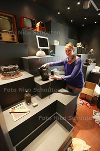 Het Stadsmuseum is aan het verbouwen. Er wordt bijvoorbeeld een schatkamer gebouwd. Conservator Marjonne Kube-van Dijk toont een antieke en nieuwe telefoon - ZOETERMEER 25 NOVEMBER 2014 - FOTOGRAFIE NICO SCHOUTEN