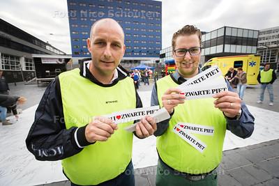 Demonstratie voor Zwarte Piet op Spuiplein - Zwarte Piet was er niet. Patrick Peezenkamp en Marc Bor (beiden Zwarte Piet) delen stickers uit - DEN HAAG 25 OKTOBER 2014 - FOTOGRAFIE NICO SCHOUTEN