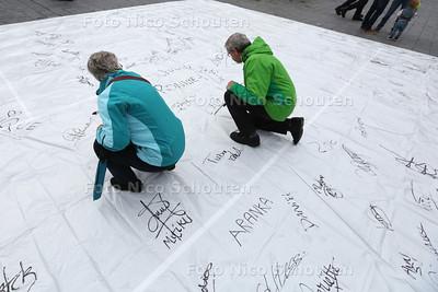 Demonstratie voor Zwarte Piet op Spuiplein - Zwarte Piet was er niet. Mensen konden hun handtekening zetten op een groot zeil - DEN HAAG 25 OKTOBER 2014 - FOTOGRAFIE NICO SCHOUTEN