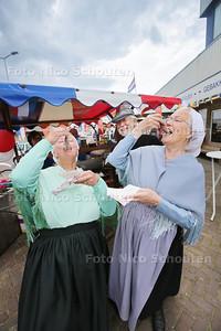 vissersvrouwen in kledingdracht, happend aan haring, Hollandse Nieuwe, in aanloop naar Vlaggetjesdag - DEN HAAG 16 JUNI 2016 - FOTO NICO SCHOUTEN