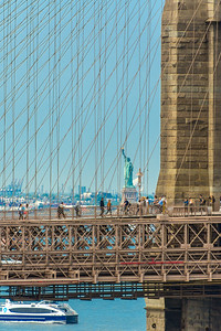 The Statue of Liberty seen through the Brooklyn Bridge