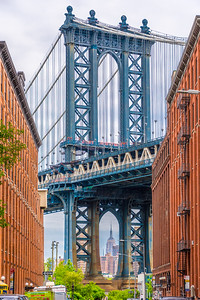 The Manhattan Bridge with the Empire State Building in between the supports