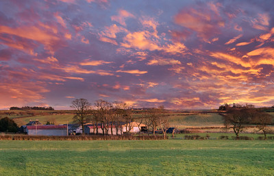 Scottish Ayrshire Fields with farm Buildings in the distance all at sunset end of the day.