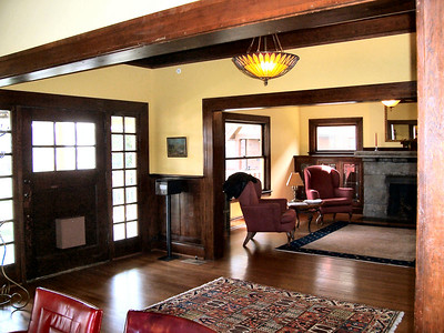 The main entrance flanked by beveled glass panels.  In the living room, the basalt stone fireplace has been completely restored.