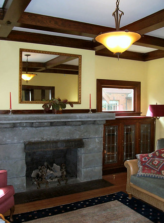The basalt stone fireplace is flanked by bookcases with elaborate leaded glass doors.