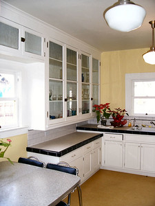 Rather than gutting the kitchen and turning it into office space, the organization restored it as a kitchen.  The upper cabinets are all original.  Note the lower counter tops at the left -- the original height.  Cabinets on the far wall are new and built to modern standards.