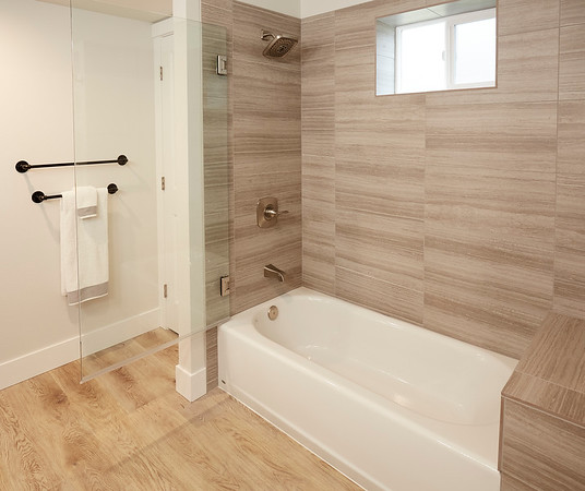 Bathroom remodel with wood floors and wood wall tiles.