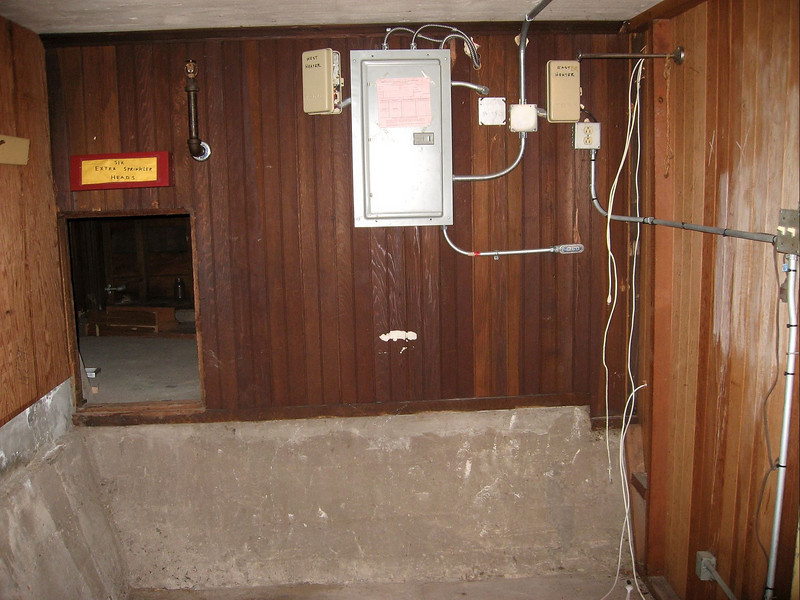 Mom, this is the little room at the front of the house on the bottom floor.  That little hole leads into the crawlspace which is under the patio entranceway area.  There's about 4 feet of clearance in the crawlspace.  That's going to be my bedroom.