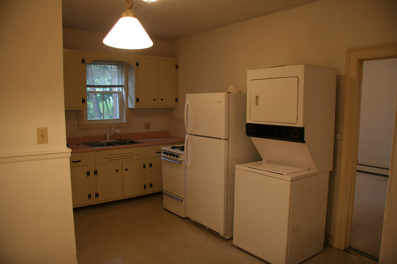 Kitchen 'before'. Note modern W/D next to back bedroom door. Convenient! Old-style cottage hardware on cabinets, linoleum, etc.