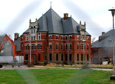 The former NSH Administration Building as shot through the chain link fence in front of it.