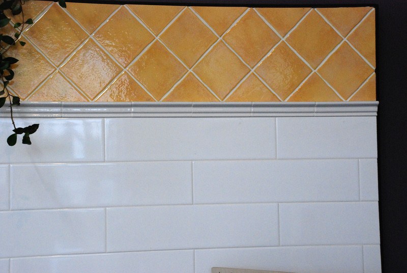 This is the style we're going for.  This was a display at Art Tile.  We were very creative shamelessly copied the entire design for our bathroom.  For scale, the yellow tiles are 4 inches by 4 inches.  The white tiles are 4 inches tall by 16 inches wide.