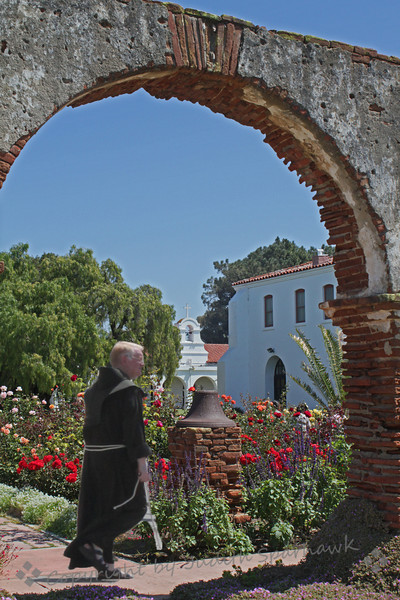Friar in the Garden ~ This view of San Luis Rey Mission shows some of the old brickwork in the archway into the rose garden.