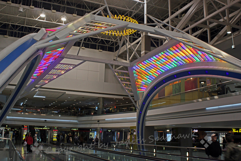 Denver Airport Colors ~ Having an unexpected 5 hour layover in Denver Airport, I took my camera out of the bag and wandered a bit.  This structure with colorful neon lights was in Terminal B, and encompassed part of the moving walkway.  I photographed it from several angles, and almost forgot to be mad about that layover....