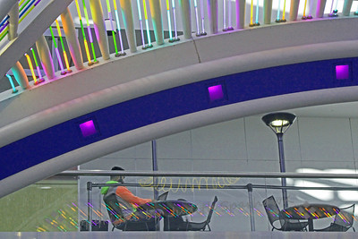Color Cafe ~ On the upstairs level, under the neon structure, a man sat relaxing with his laptop in the cafe.  I liked the reflections of the lights on the glass below.  Denver International Airport.