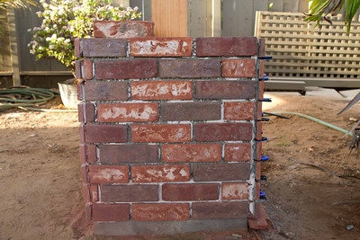 """An example of McGirrs Construction quality:  requests for the """"masonry/tile sub"""" contractor's license never materialized.  Ben Hernandez Masonry is likely unlicesnsed.  With L shaped veneer brick sitting on the job, he couldn't figure out how to use them so left vertical seams instead."""
