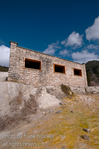 On a little knoll about a minute's hike up from the Fairmont Hot Springs parking lot, lies a real treasure. Sitting on a plateau of tufa rock coloured orange, brown, green and blue by the streams of spring water that leap out of the rocks above, is a very old stone bathhouse.<br /> <br /> Fairmont Indian baths are natural hot spring pools that were popular among early settlers of the valley. It is not known why they were called 'Indian' baths. At the time that explorer David Thompson described them in his journal, there was no building.
