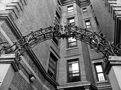 Wrought iron entry arch, Bona Vista Court, Washington Heights, NYC  iPhone photo  Built in 1905, the Bona Vista Court apartment building at 945 St. Nicholas Avenue has always intrigued me. The unusual wrought iron arch over its entryway embeds the building's name on its underside, and the peak of its curve appears to have once contained a lantern. On September 16, 1920, a time bomb detonated outside the offices of J.P. Morgan at 23 Wall Street, killing 38 people. The perpetrators, believed to have been Italian anarchists, were never found out. But one man living in this building was listed among the numerous injured employees of the Equitable Trust Company; George Williams, who suffered cuts, became the personal link from a giant bit of history exploding ten miles away to this little Washington Heights apartment building.