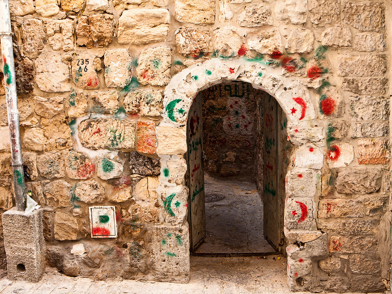 An archway to an alley is decorated with a variety of markings that indicate that the inhabitants have visited various landmarks on Hajj, or pilgrimage, journeys for the Islamic faithful.